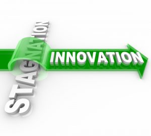 The word Innovation on an arrow jumping over the word Stagnation, symbolizing the forward motion of creative change over the status quo